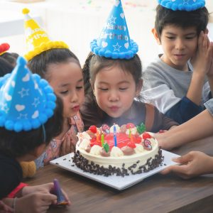 Group of kid friends is blowing birthday cake