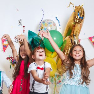 Group of smiling children throwing confetti around them