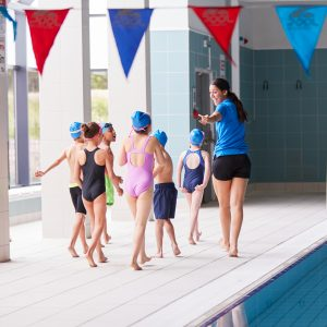 Female Coach Walks Children In Swimming Class Along Edge Of Indoor Pool