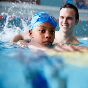 Male Swimming Coach Giving Boy Holding Float One To One Lesson In Pool